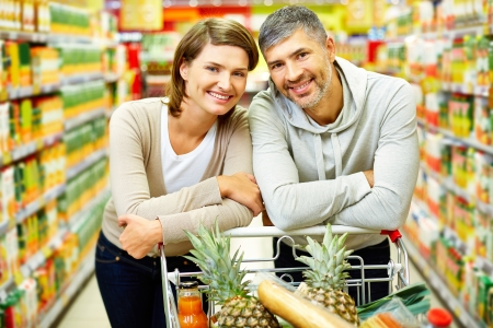 Image of happy couple with cart looking at camera in supermarket photo