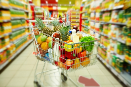 market: Image of cart full of products in supermarket Stock Photo