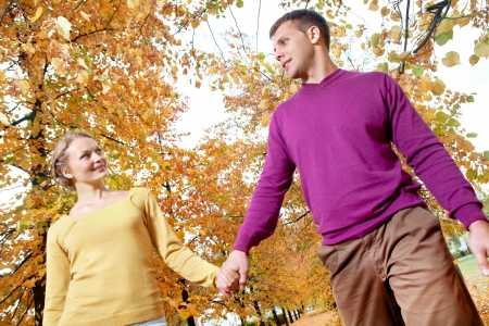 Portrait of young couple walking in autumnal park photo