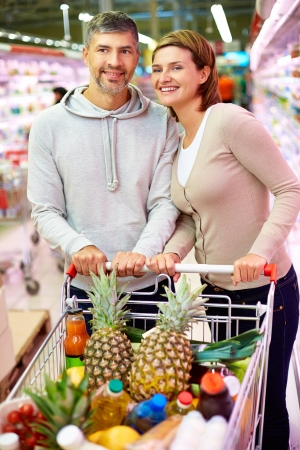 Image of happy couple with cart choosing products in supermarket photo