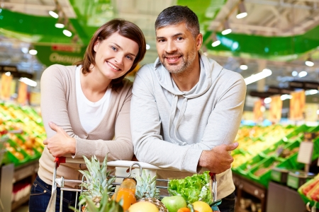 Image of happy couple with cart full of products looking at camera in supermarket Stock Photo - 20137412