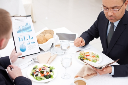 lunch meeting: Confident businessmen planning work at business lunch Stock Photo