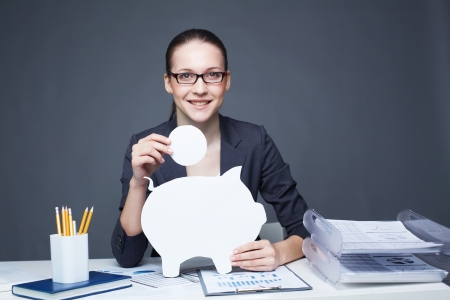 Portrait of young smiling female with paper piggy bank and coin looking at camera photo