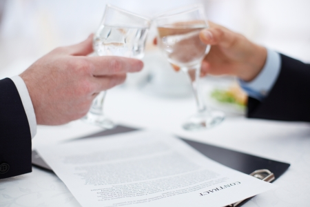 Image of businessman hands toasting with glasses with signed contract near by photo