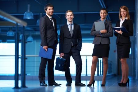 事務所ビルのラインに立ってのスーツでフレンドリーなビジネスマンのグループ