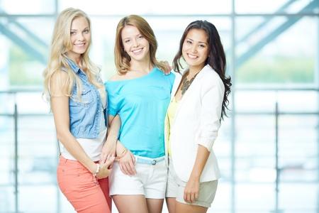 Retrato de tres niñas felices en ocasional elegante mirando a la cámara
