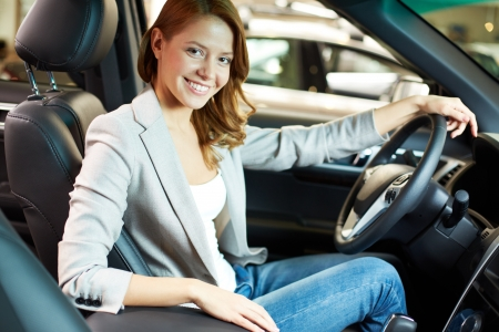 Photo of elegant woman sitting in a new car in automobile center photo