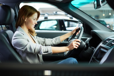 Photo of young woman choosing a new car in automobile center photo