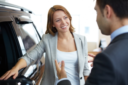 car dealers: Photo of elegant woman speaking to consultant in automobile center Stock Photo