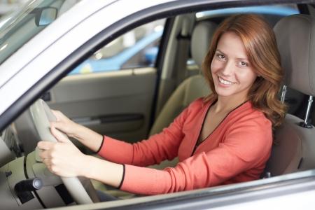 新しい車の中で座っていると、カメラを見てかわいい女性の写真 写真素材