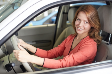 car transmission: Photo of cute woman sitting in a new car and looking at camera