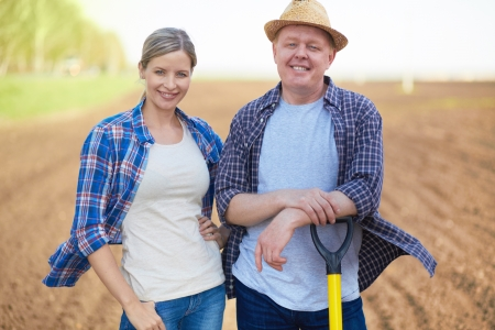 Image of two happy farmers on background of plowed field photo