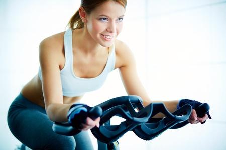 mujer sola: Retrato de la formaci?e j?es mujeres en el simulador en el gimnasio Foto de archivo