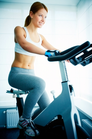 simulator: Image of young female training on simulator in gym Stock Photo