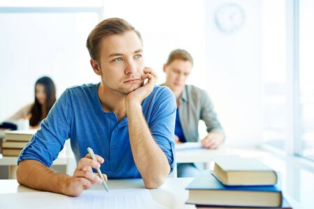 Portrait of handsome student carrying out test at lesson photo