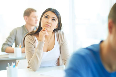 Portrait of pensive student thinking of right answer at lesson