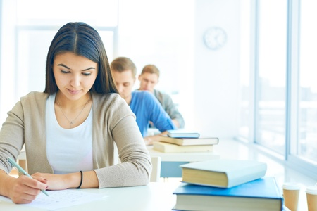 Portrait of pensive student carrying out test at lesson Stock Photo