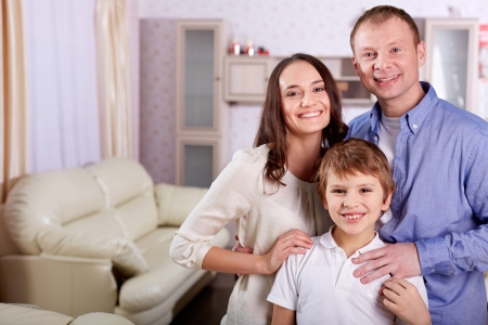 Portrait of happy family of three looking at camera at home Stock Photo - 20259125