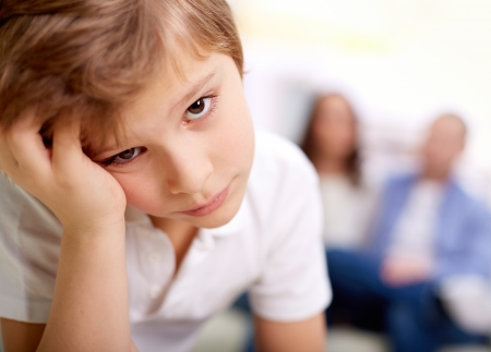 Portrait of sad boy looking at camera on background of his parents photo