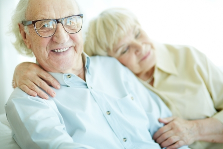smiley faces: Happy elderly man looking at camera with his wife on background Stock Photo