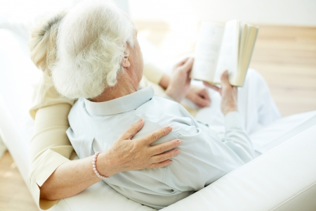 Grey-haired elderly man and his wife reading book at home photo