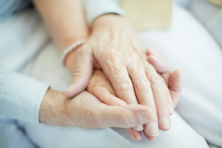 unrecognized: Close-up of senior male holding the hand of his wife