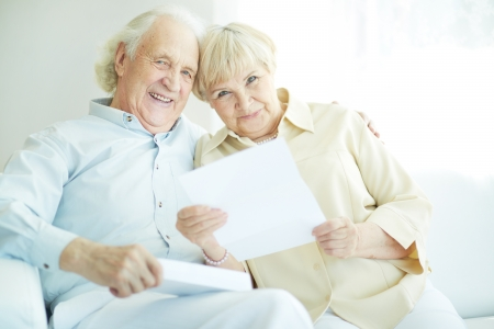mail man: Portrait of a candid senior couple with paper looking at camera