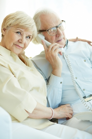 committed: Portrait of elderly woman looking at camera with her husband talking on the phone near by