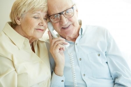 Portrait of elderly man looking at camera awhile talking on the phone with his wife near by photo