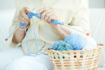 clew: Hands of elderly woman knitting woolen clothes Stock Photo