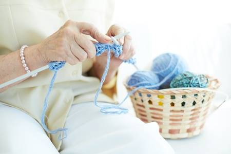 basket embroidery: Hands of elderly woman knitting woolen clothes Stock Photo