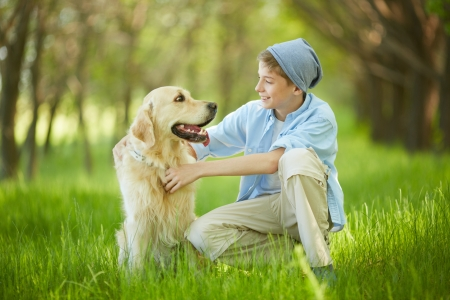 Portrait of cute lad embracing his white Labrador and looking at it photo