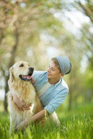 lad: Portrait of cute lad embracing his white Labrador and looking at it Stock Photo