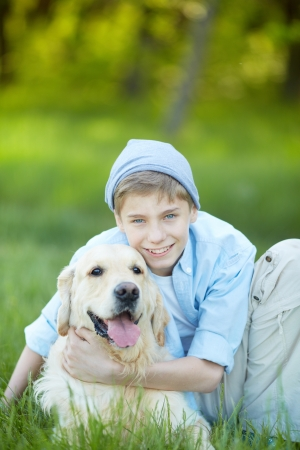 lad: Portrait of cute lad embracing his fluffy friend and looking at camera
