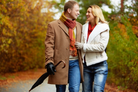 couples outdoors: Portrait of affectionate couple taking a walk in autumnal park Stock Photo