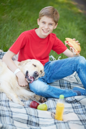 lad: Portrait of cute lad and his fluffy friend having picnic