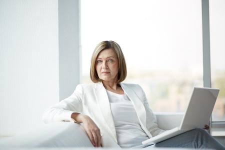 mujeres sentadas: Retrato de mujer madura con ordenador portátil mirando a la cámara
