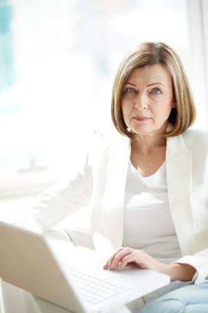 Portrait d'une femme d'?ge m?r avec un ordinateur portable en regardant la cam?ra Banque d'images - 20258953