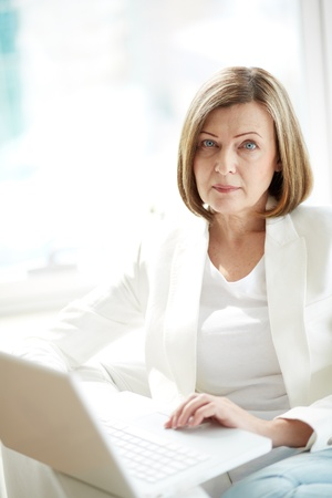 serious woman: Portrait of mature woman with laptop looking at camera