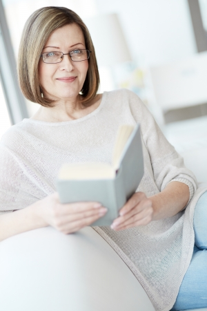 Portrait of mature woman with book looking at camera photo