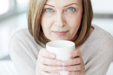 serenity: Portrait of mature woman with cup looking at camera Stock Photo