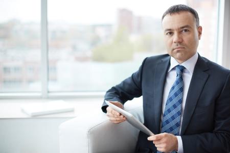 オフィスに座っているタッチパッドとエレガントなビジネスマンの肖像画