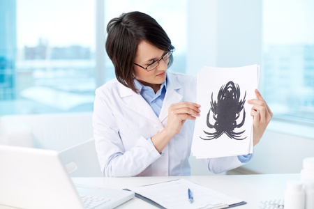 clinical psychology: Young psychologist looking at paper with Rorschach inkblot