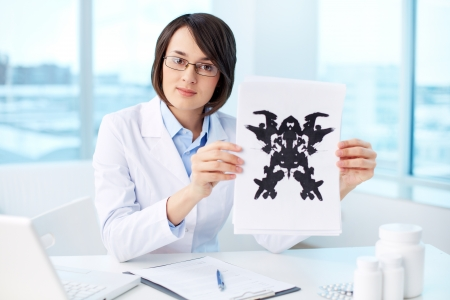 diagnosing: Serious psychologist showing paper with Rorschach inkblot Stock Photo