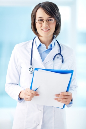 general practitioner: Vertical portrait of a lovely general practitioner holding papers Stock Photo