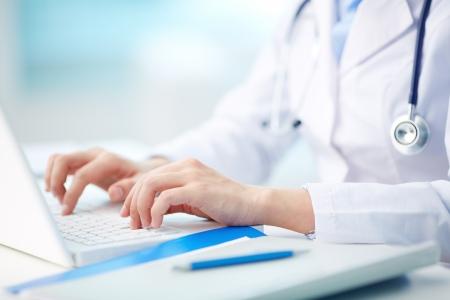 ノート パソコンに入力する医療従事者のクローズ アップ 写真素材