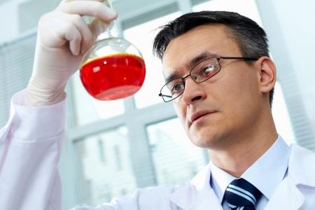 material de vidrio: Cl?nico grave mirando frasco con l?quido de color rosa en el laboratorio