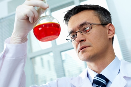 glassware: Serious clinician gazing at flask with pink liquid in laboratory Stock Photo