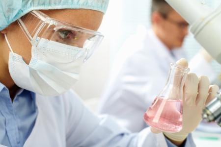 Chemist holding sample of liquid in laboratory Stock Photo