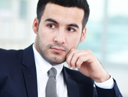 Close-up of handsome businessman with pensive expression photo